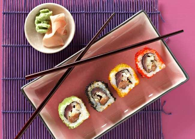 chopsticks on plate of sushi