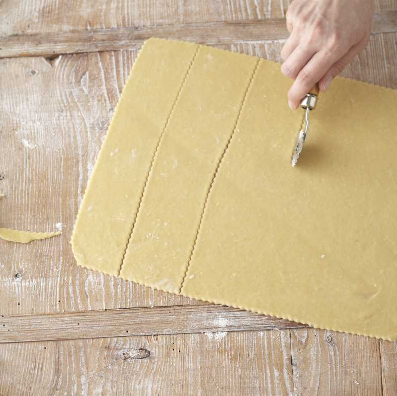 cutting dough into strips for ravioli