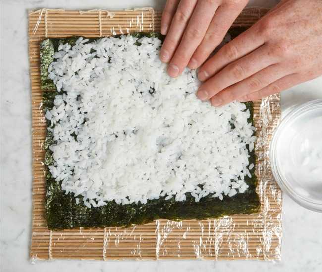 Spreading sushi rice onto nori