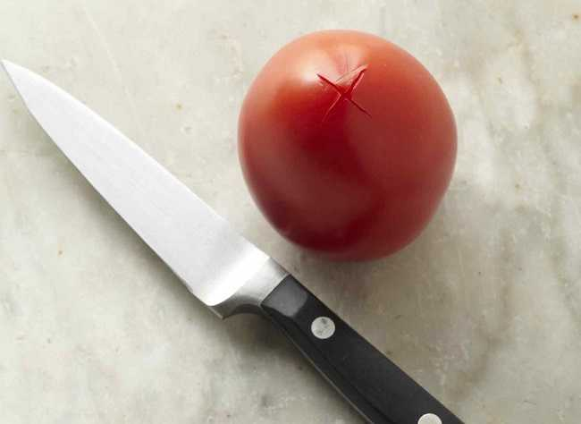 tomato with x cut into the base with knife